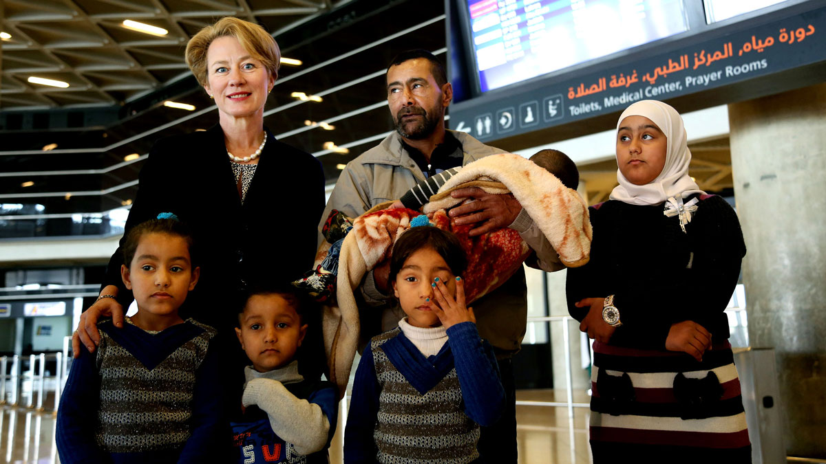 U.S. Ambassador to Jordan Jordan Alice Wells (top left) poses for a photo with Syrian refugee Ahmad al-Abboud (top center) and his family at the International Airport of Amman, Jordan, on April 6, 2016. The first Syrian family to be resettled to the U.S. under its speeded-up