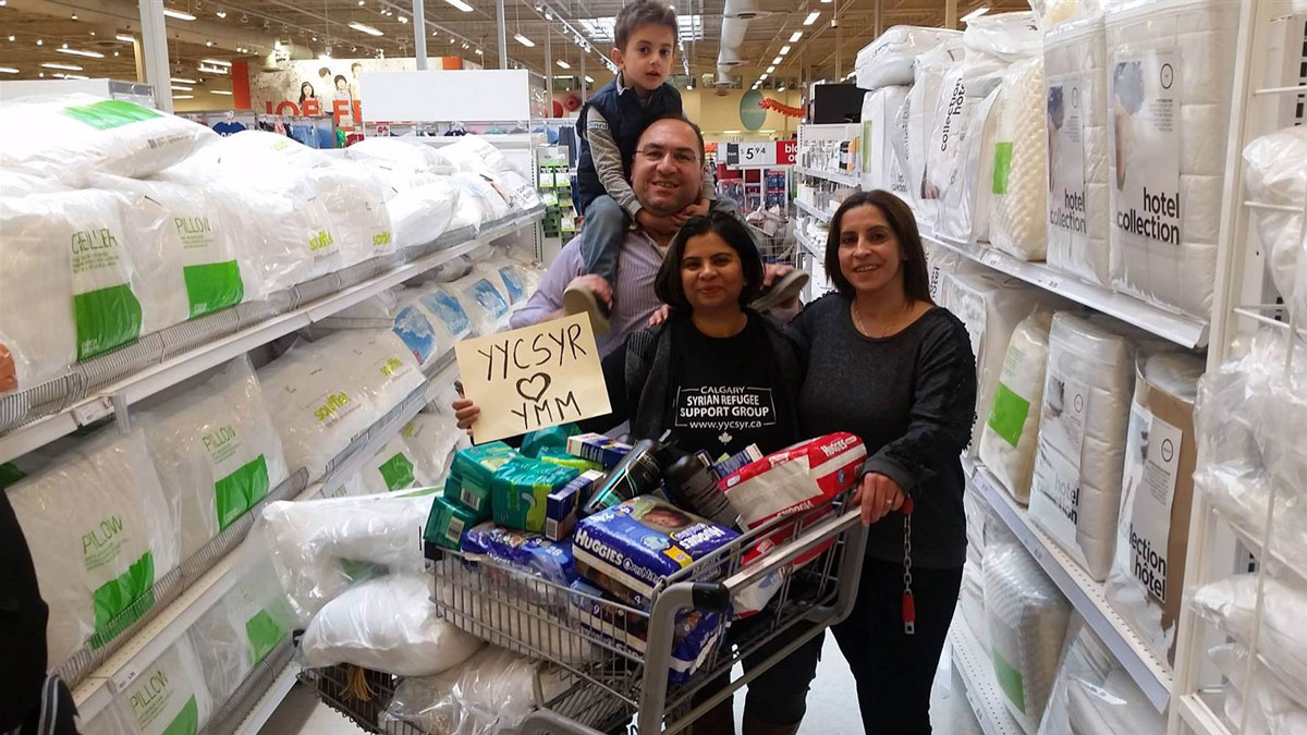 Saima Jamal, right, stands with Syrian newcomers Naser Nader and Rita Khallas as they shop for Fort McMurray evacuees. The sign they're holding up means