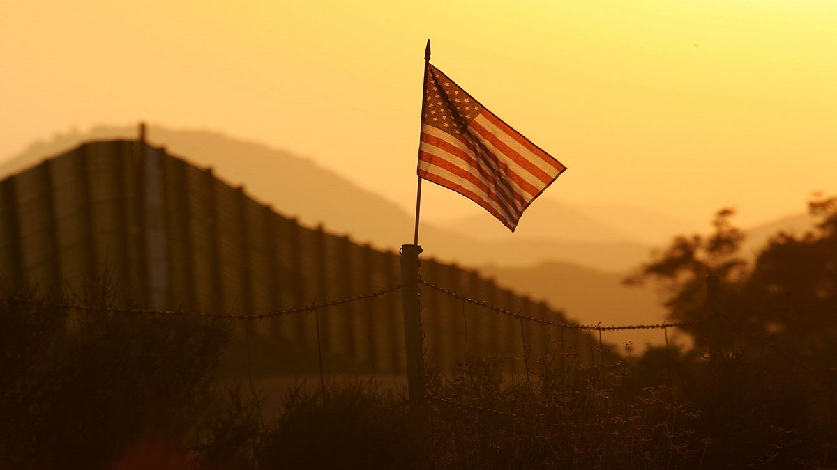 A U.S. flag put up by activists who oppose illegal immigration flies near the US-Mexico border fence in an area where they search for border crossers October 8, 2006 near Campo, California. President Donald Trump's promise of building a wall between Mexico and the United States is just one potential option for border security.
