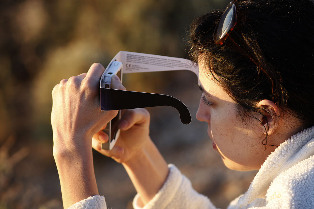 A woman checks her smart phone while watching the first annular eclipse seen in the U.S. since 1994 with special glasses to protect her eyes on May 20, 2012 in Grand Canyon National Park, Arizona.