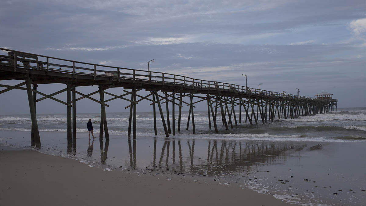 A beachcomber walks by the Oceanana Fishing Pier in Atlantic Beach, N.C., Friday, July 04, 2014. Hurricane Arthur began moving offshore and away from North Carolina's Outer Banks early Friday after hitting the state's barrier islands overnight and causing flooding and thousands of power outages.