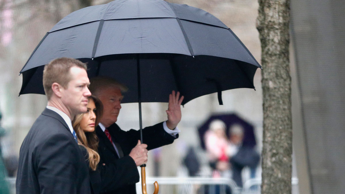 Republican presidential candidate Donald Trump, right, waves as he walks with his wife Melania Trump, center, during his arrival to the World Trade Center Museum, Saturday, April 9, 2016, in New York.
