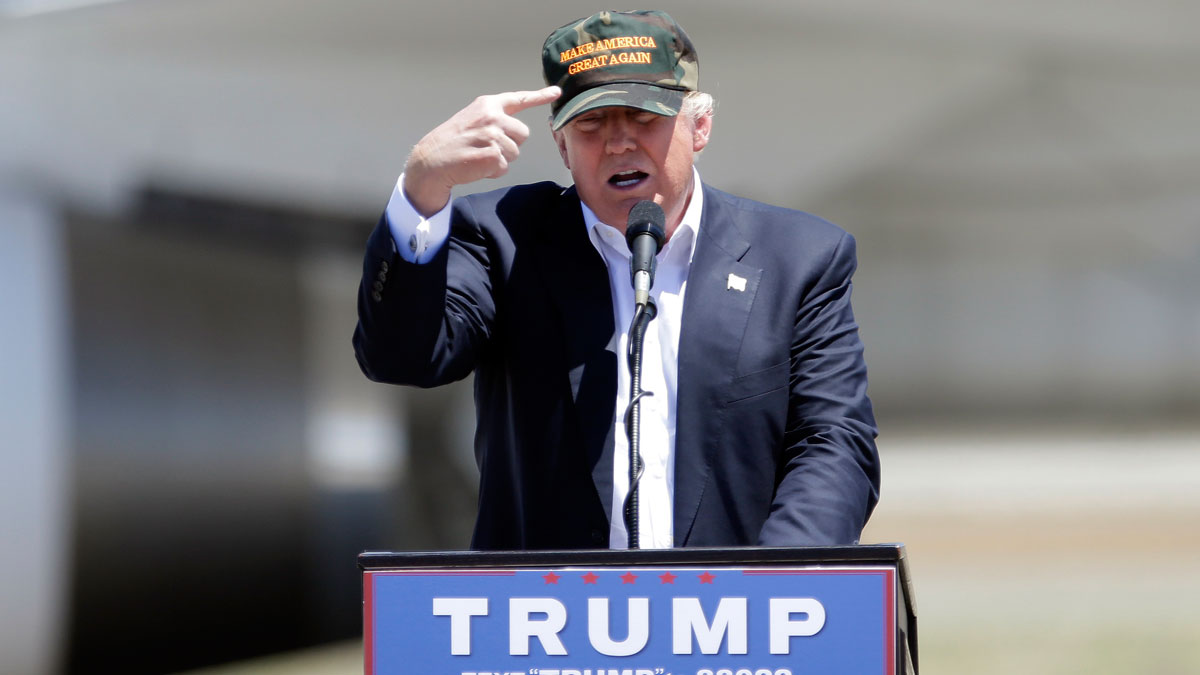 Republican presidential candidate Donald Trump gestures to a his camouflaged