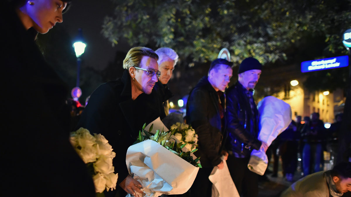 Bono and band members from the band U2 place flowers on the pavement near the scene of yesterday's Bataclan Theatre terrorist attack on November 14, 2015 in Paris, France. At least 120 people have been killed and over 200 injured, 80 of which seriously, following a series of terrorist attacks in the French capital.