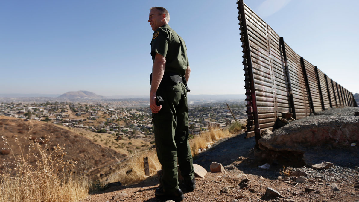 In this June 13, 2013 file photo, US Border Patrol agent Jerry Conlin looks out over Tijuana, Mexico, along the old border wall along the US - Mexico border, where it ends at the base of a hill in San Diego. In 2015, U.S. Customs and Border Protection employees apprehended more than 2,000 immigrants not from Mexico crossing the border illegally. In just the first four months of 2016 there were more than 2,500 such immigrants apprehended.