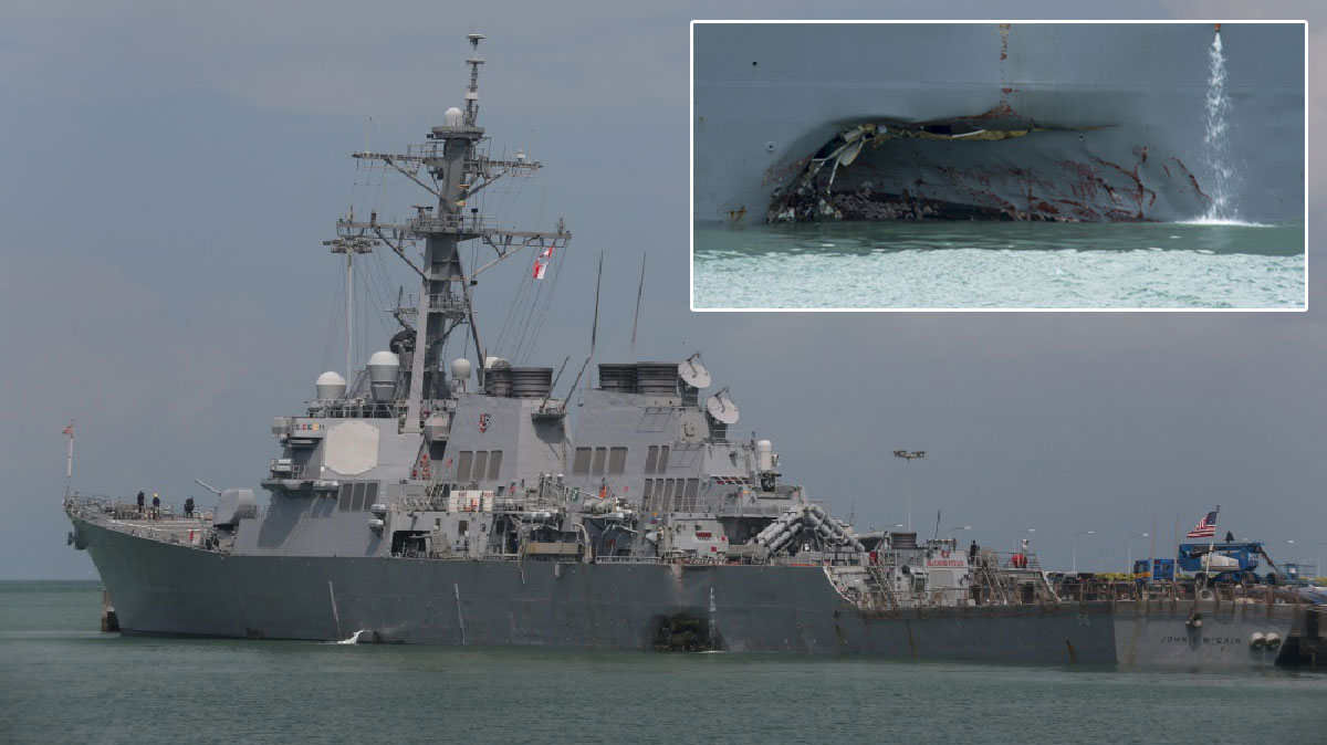 The destroyer USS John S. McCain arrives at Changi Naval Base on Monday, August 21, 2017, in Singapore with visible damage to the port side after a collision with an oil tanker.