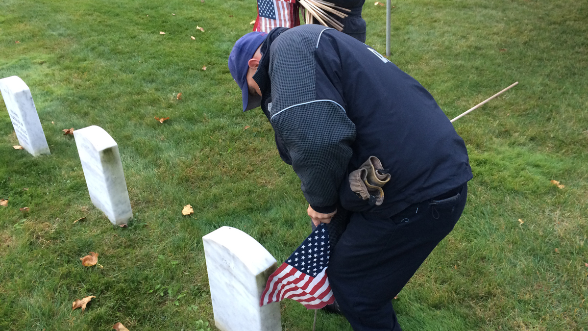 Volunteers knelt down to place a small American flag next to the headstones of the 10,000 veterans buried in the state's veterans' cemetery.