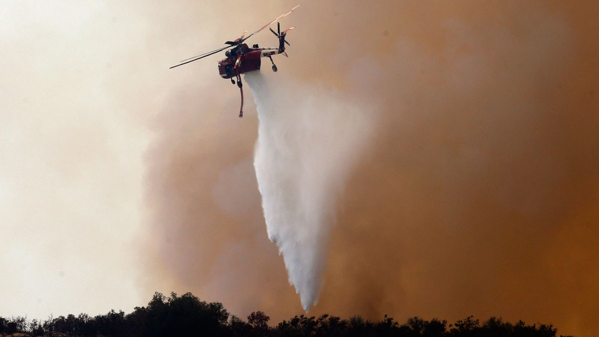 A firefighting helicopter makes a water drop to help combat a wildfire near Santa Barbara, Calif., on Friday, June 17, 2016. Stoked by winds, a wildfire burning west of Santa Barbara roared down mountain slopes toward the Pacific Ocean, shutting down California's major coastal highway and forcing a group of firefighters to seek shelter behind a fire engine as flames licked at them.