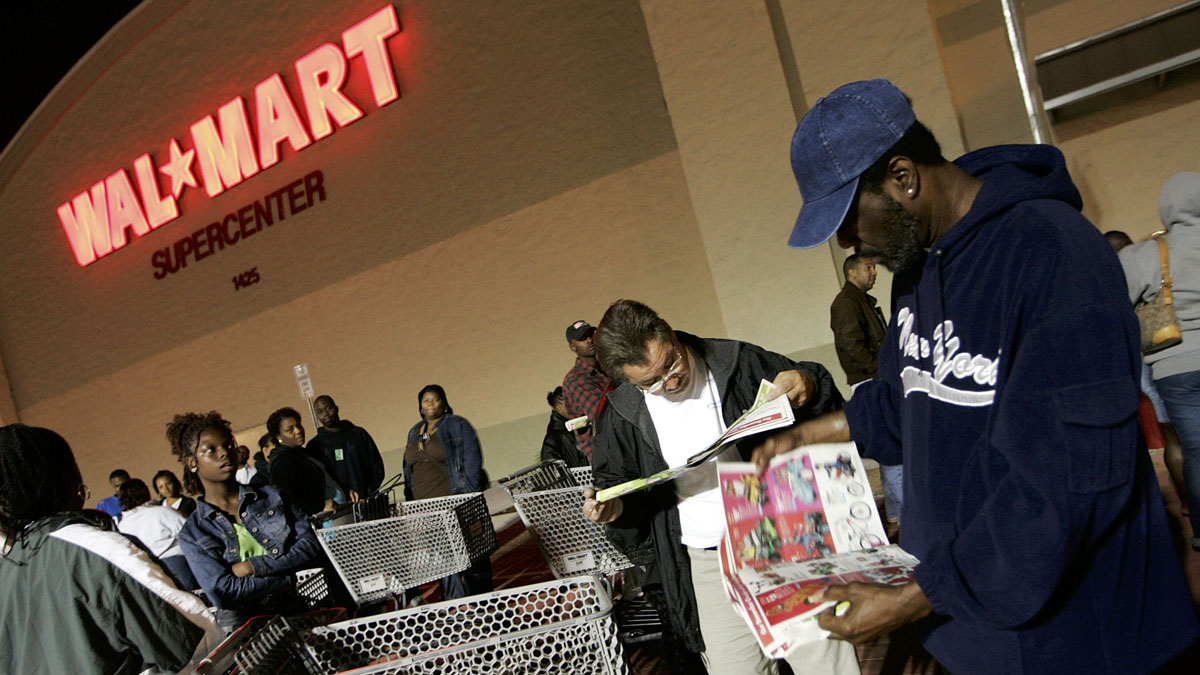 MIAMI - NOVEMBER 25:  People stand in front of a Walmart store before the doors open at 5am on the day known as