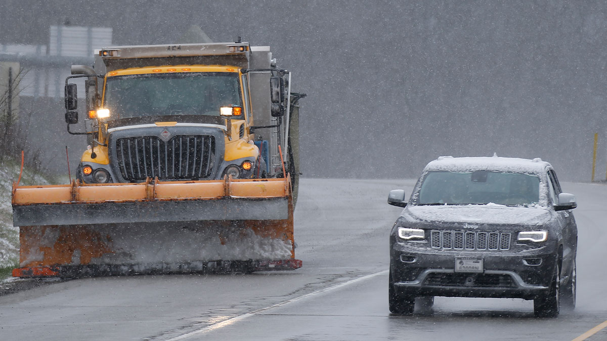 Traffic drives past a plow truck on an exit ramp as snow falls along Interstate 79 in Zelienople, Pa. on Saturday, April 9, 2016.