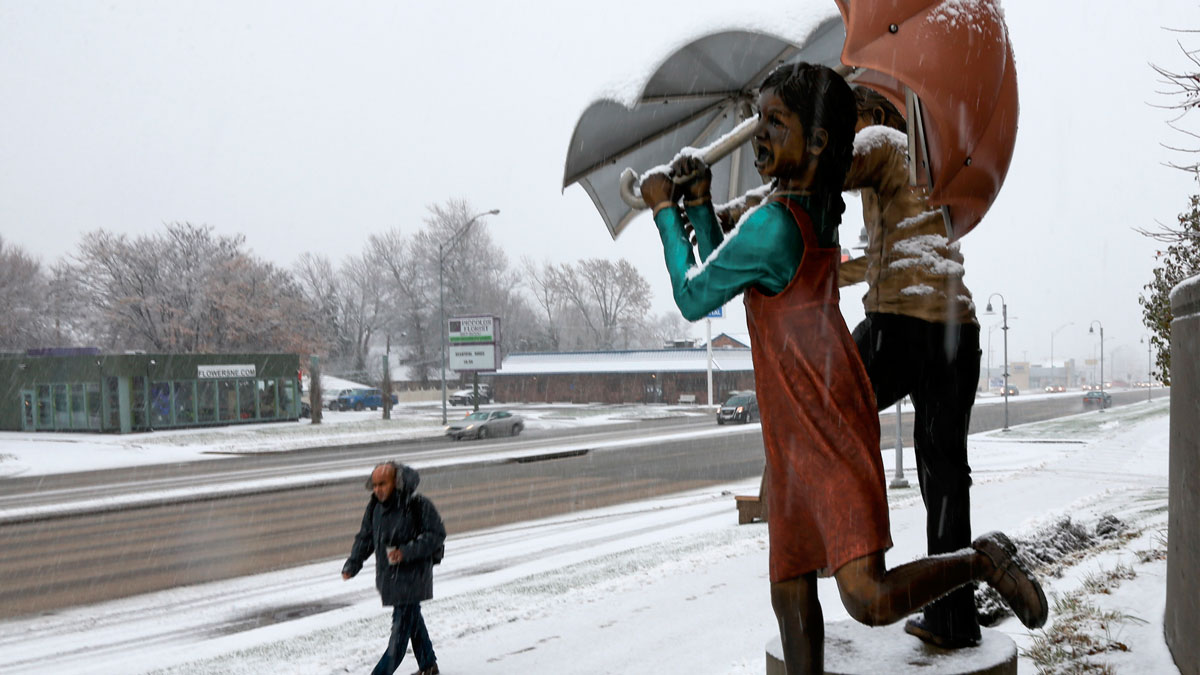 A man walks in the snow past a statue of children holding umbrellas in Omaha, Neb., Monday, Nov. 30, 2015. A slow-moving wintry storm system has been moving through parts of the Plains and the Midwest since Thursday.