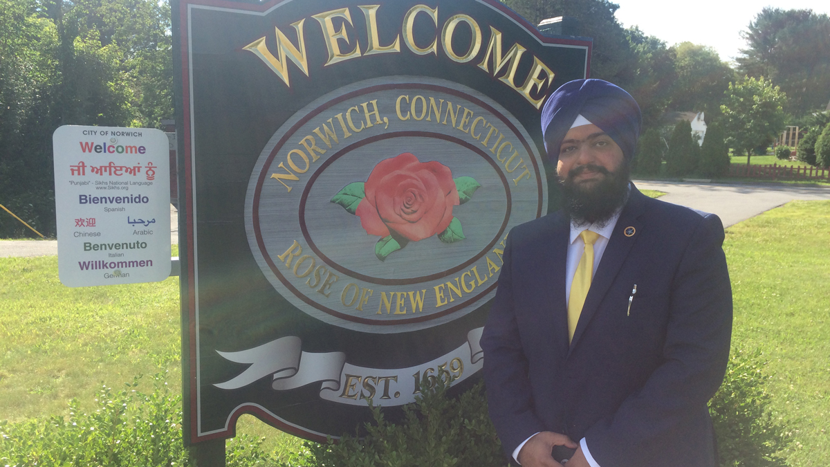 Swaranjit Singh Khalsa stands with one of two multi-lingual welcome signs he's worked to have installed in Norwich.