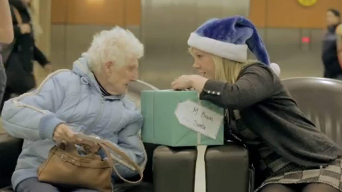 A screen shot of the video that captured lucky passengers opening their surprise Christmas presents at the airport.