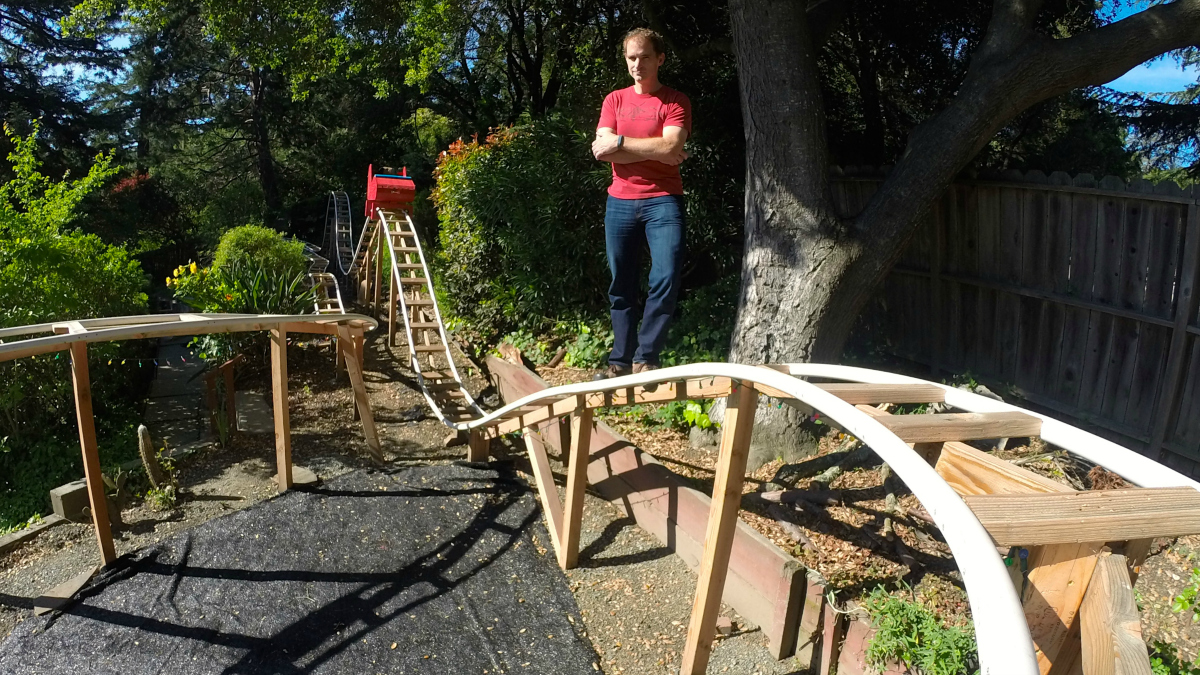 Will Pemble stands in his Orinda backyard with his handmade roller coaster.