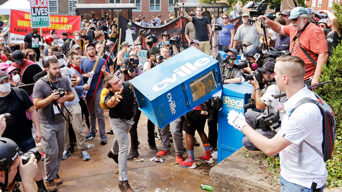 In this Aug. 12, 2017, file photo, white nationalist demonstrators, right, clash with a counter demonstrator as he throws a newspaper box at the entrance to Lee Park in Charlottesville, Virginia.