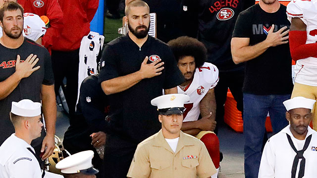 Colin Kaepernick, teammate kneel during national anthem.