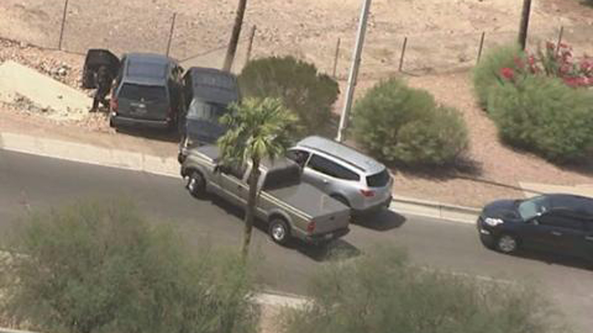 Authorities surround an SUV that led police on a chase through the Phoenix area Tuesday, September 6, 2016. At least one officer opened fire on the SUV after the chase came to an end, killing one person.
