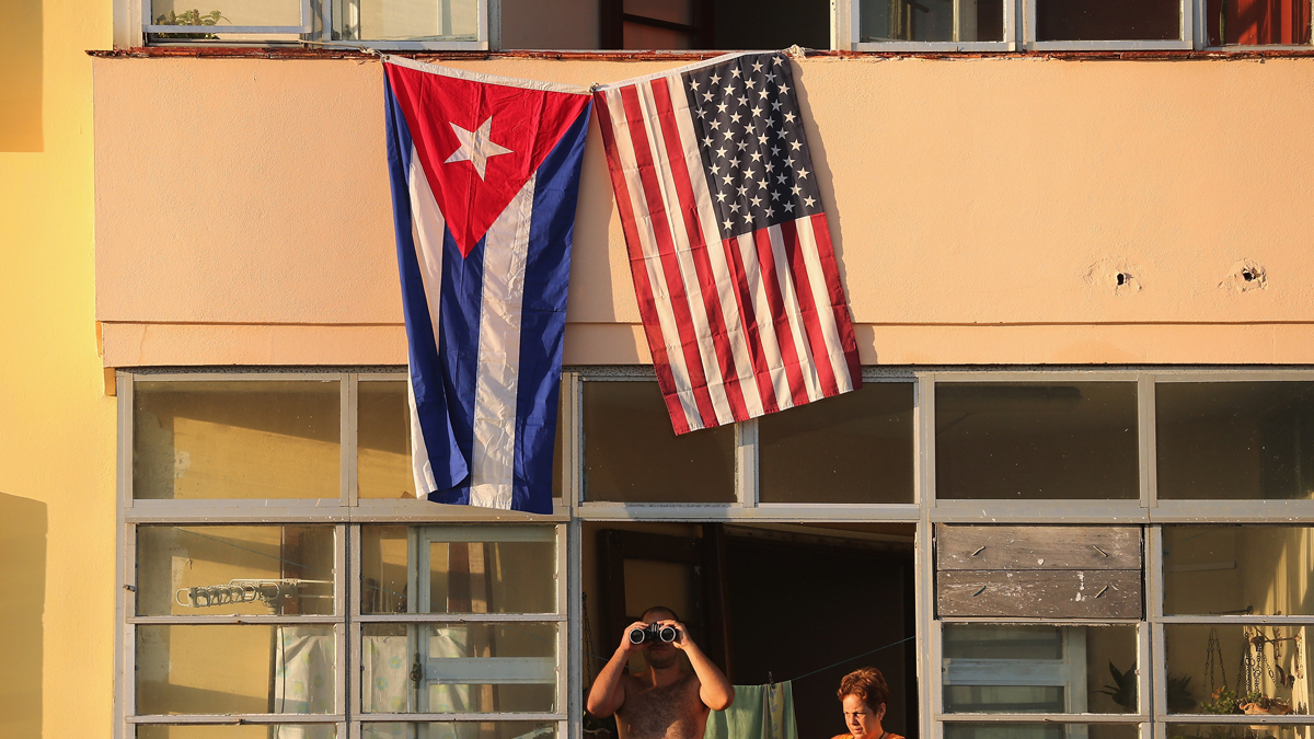 Cubans look out their window across the street from the newly reopened U.S. Embassy in hopes of watching the flag-raising ceremony in 2015. Donald Trump is expected to roll back diplomatic and business ties with Cuba Friday.
