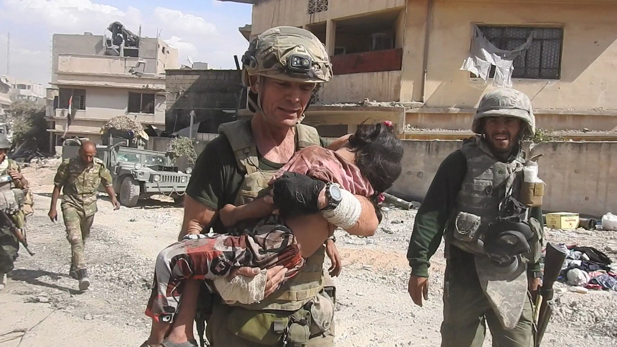 Dave Eubank, a volunteer aid worker and founder of the Free Burma Rangers, carries a young girl he rescued amid a wave of ISIS sniper fire on June 2, 2017, in Mosul, Iraq.