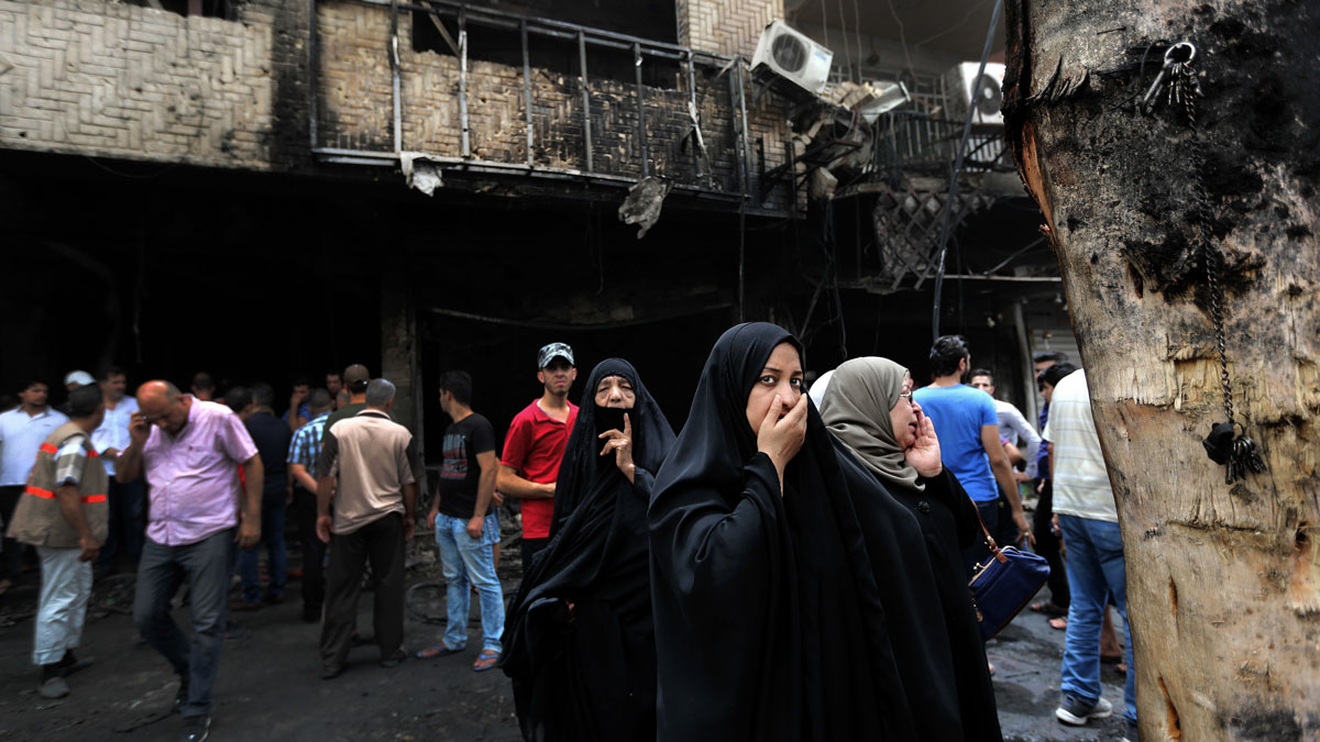 File - Iraqi women wait to hear about family members who went missing after a car bomb hit Karada, a busy shopping district in the center of Baghdad, Iraq, Sunday, July 3, 2016.