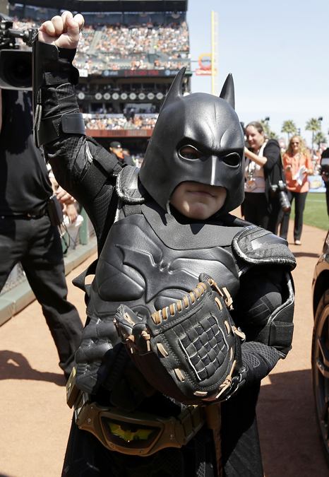 Miles Scott, dressed as Batkid, right, walks with Batman before saving a damsel in distress in San Francisco, Friday, Nov. 15, 2013.  San Francisco turned into Gotham City on Friday, as city officials helped fulfill Scott's wish to be