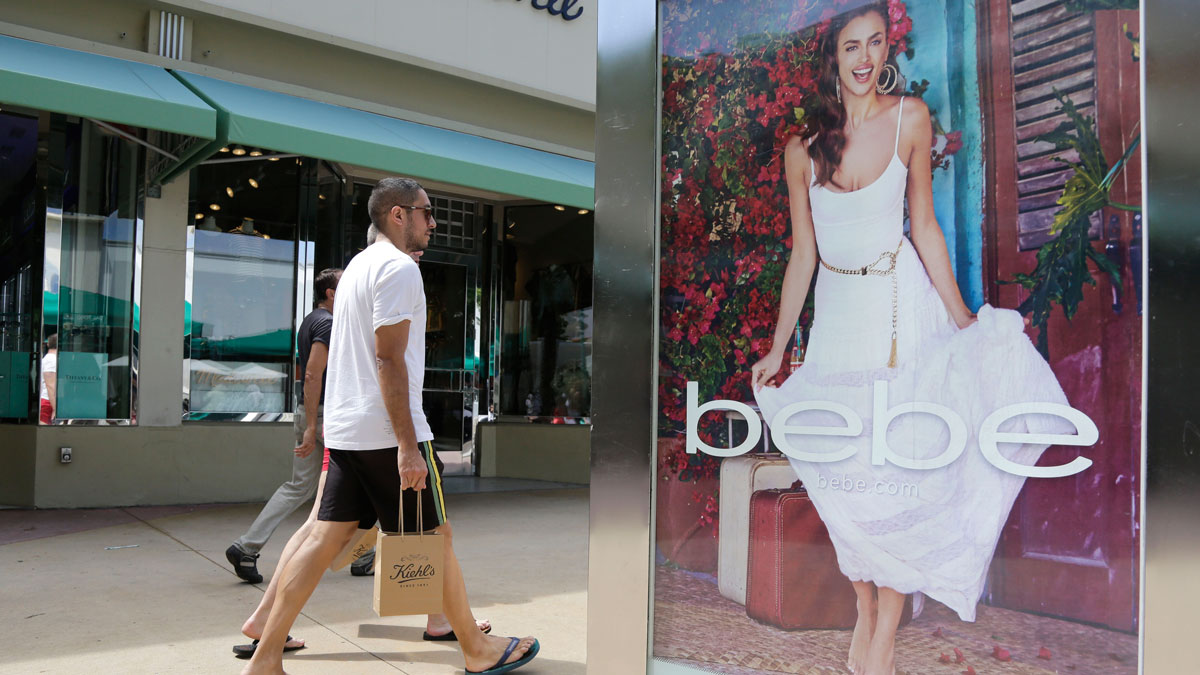 In this March 13, 2015 file photo, shoppers walk past an advertisement for retailer