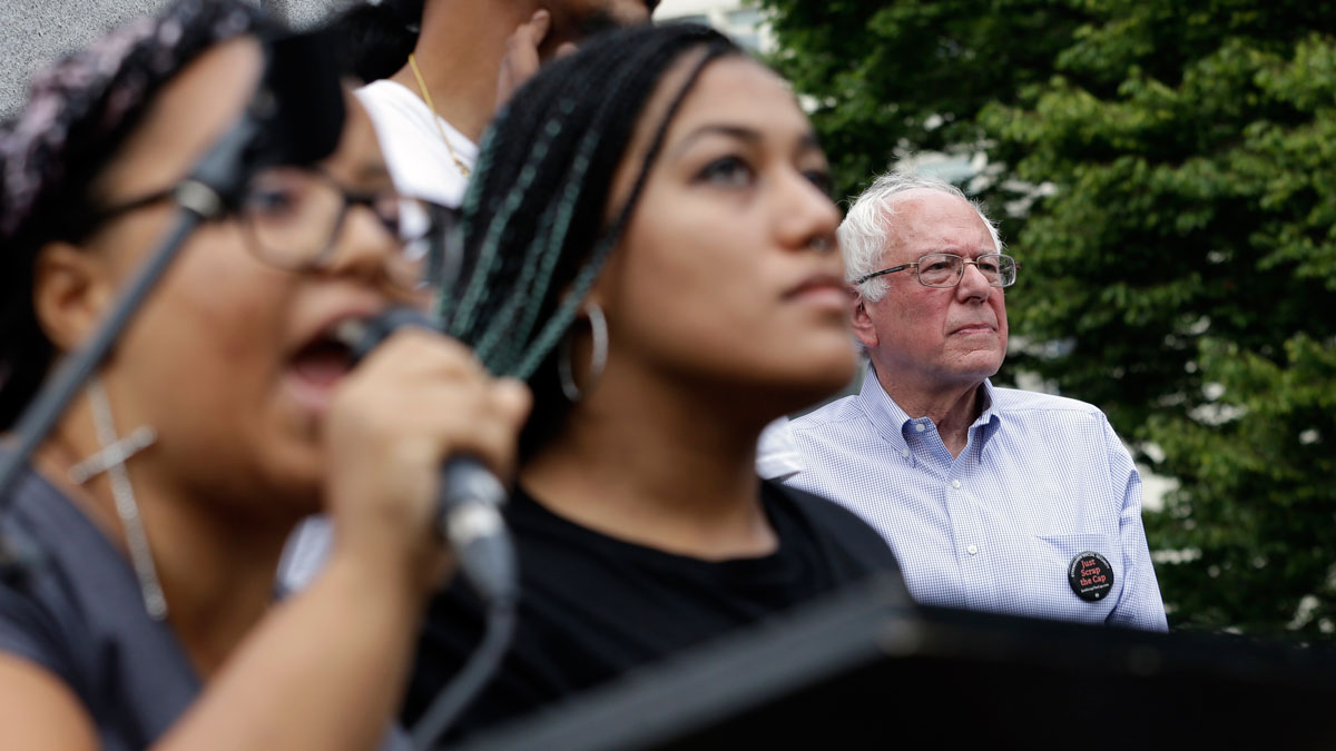 Marissa Johnson, left, speaks as Mara Jacqueline Willaford stands with her and Democratic presidential candidate Sen. Bernie Sanders, I-Vt., stands nearby as the two women take over the microphone at a rally Saturday, Aug. 8, 2015, in downtown Seattle. The women, co-founders of the Seattle chapter of Black Lives Matter, took over the microphone moments after Sanders began speaking and refused to relinquish it. Sanders eventually left the stage without speaking further and instead waded into the crowd to greet supporters.