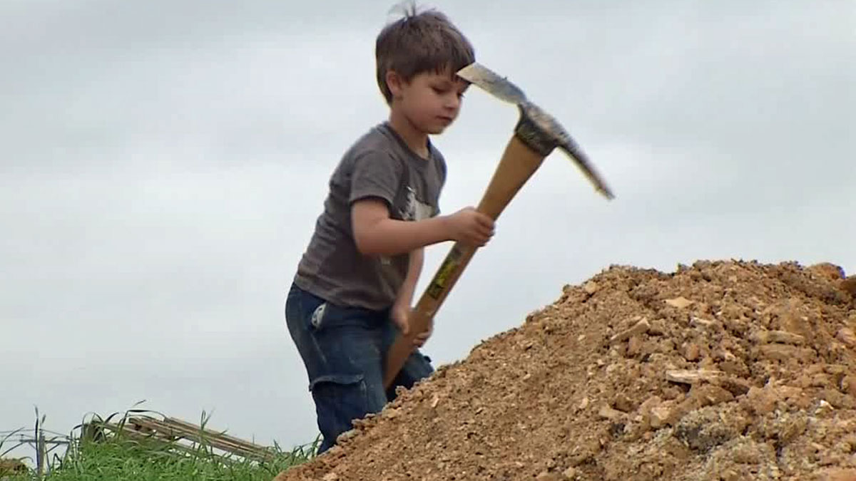 Wiley Brys, 4, digs for dinosaur bones in Mansfield.