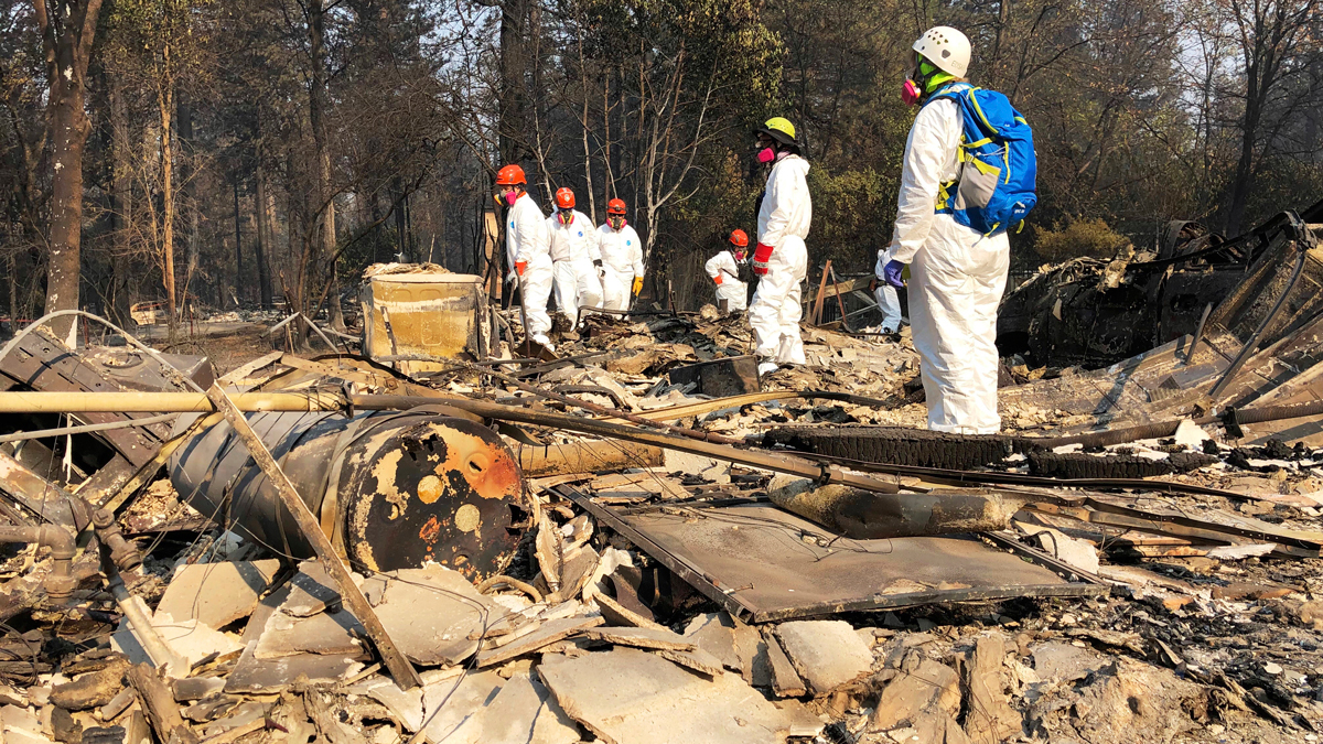 In this Nov. 18, 2018 file photo, volunteer members of an El Dorado County search and rescue team search the ruins of a home, looking for human remains, in Paradise, Calif., following a wildfire.
