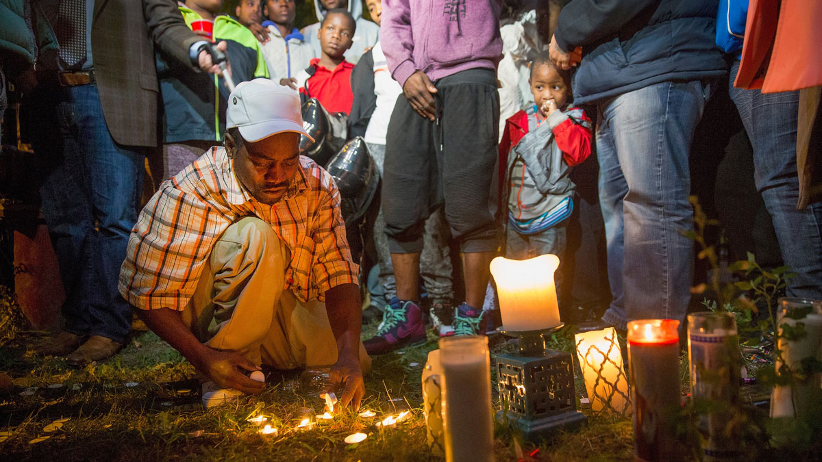 Darnell Wells lights a candle to remember his 24-year-old niece Patricia Chew and her 46-year-old mother, his sister, Lolita Wells, at a memorial service where they were shot and killed on September 29, 2015, in Chicago. The two were among five people shot at the scene including Chew's 11-month-old son. Chew was reported to be two months pregnant when she was killed.