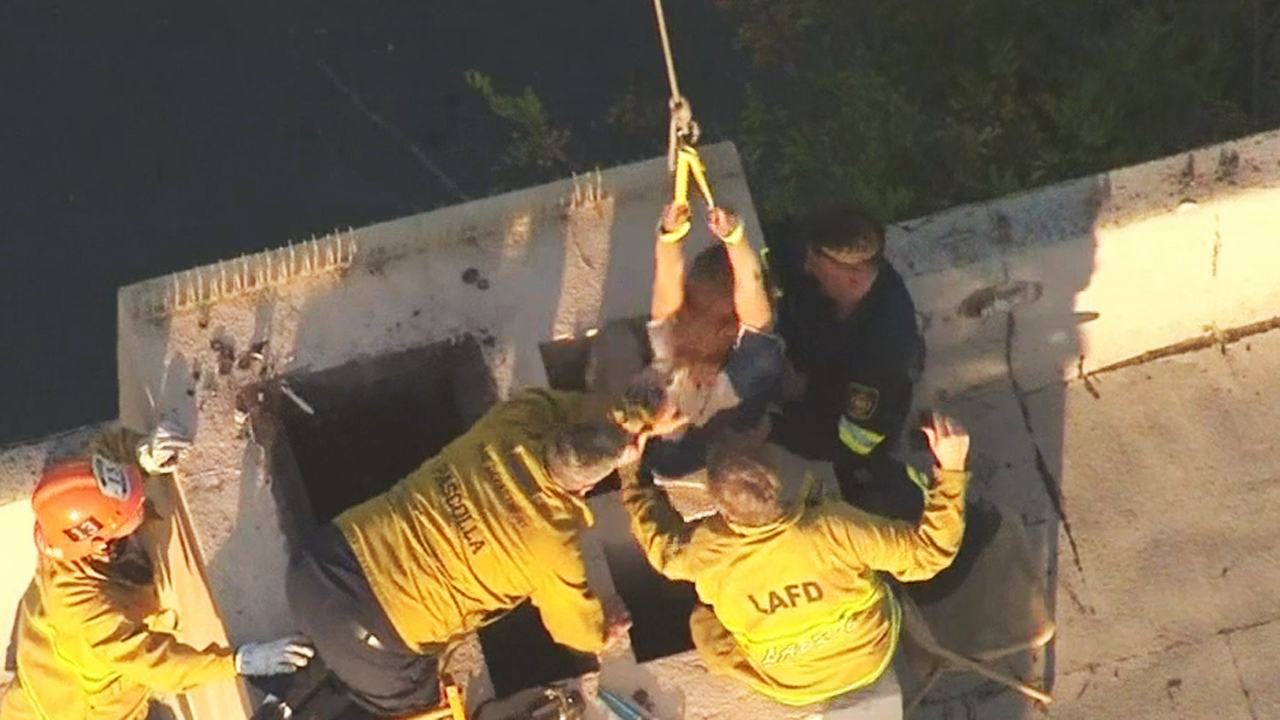 Los Angeles firefighters free a woman who became stuck in a school chimney on Saturday, May 30, 2015.