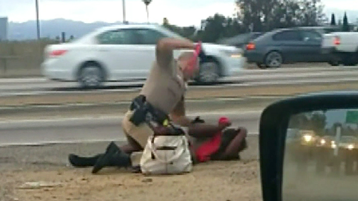 A video posted to YouTube shows a California Highway Patrol officer hitting a woman after responding to a call about a pedestrian on the freeway in Los Angeles July 1, 2014.