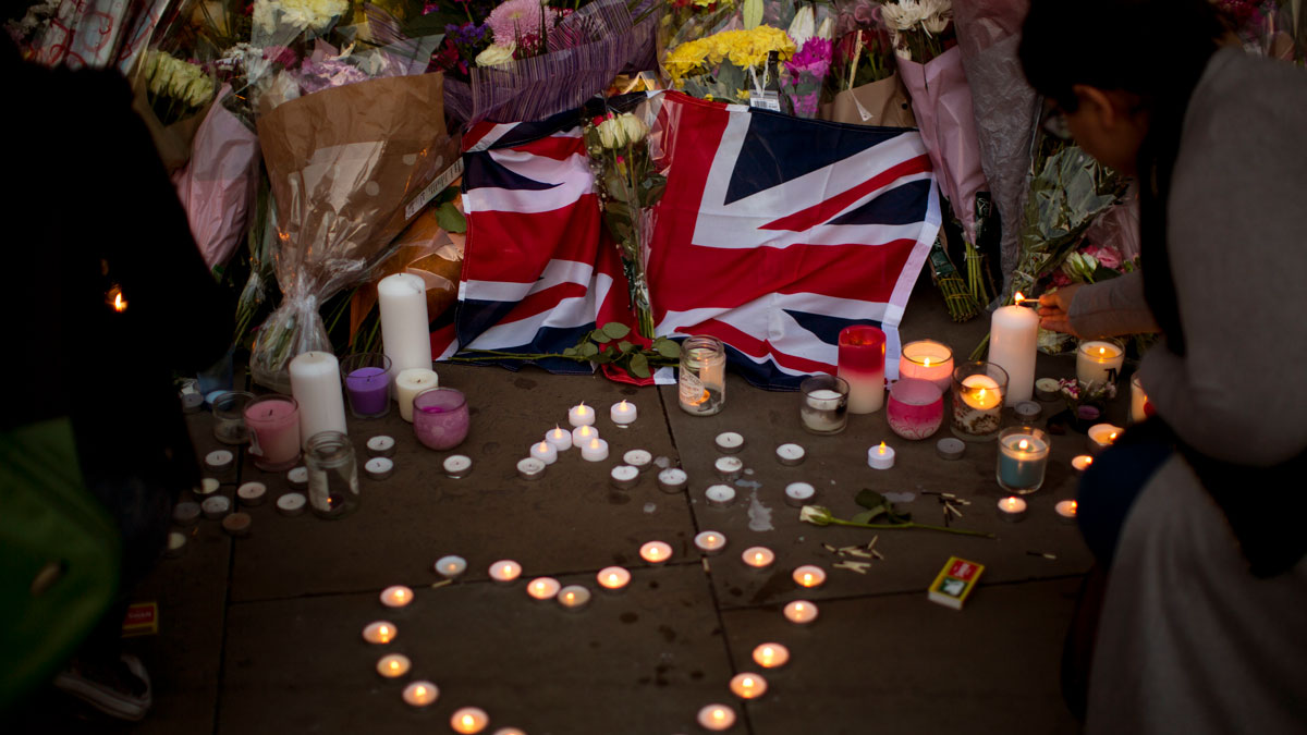 A British flag is seen next to flowers after a vigil in Albert Square, Manchester, England, Tuesday May 23, 2017, the day after the suicide attack at an Ariana Grande concert that left 22 people dead as it ended on Monday night.