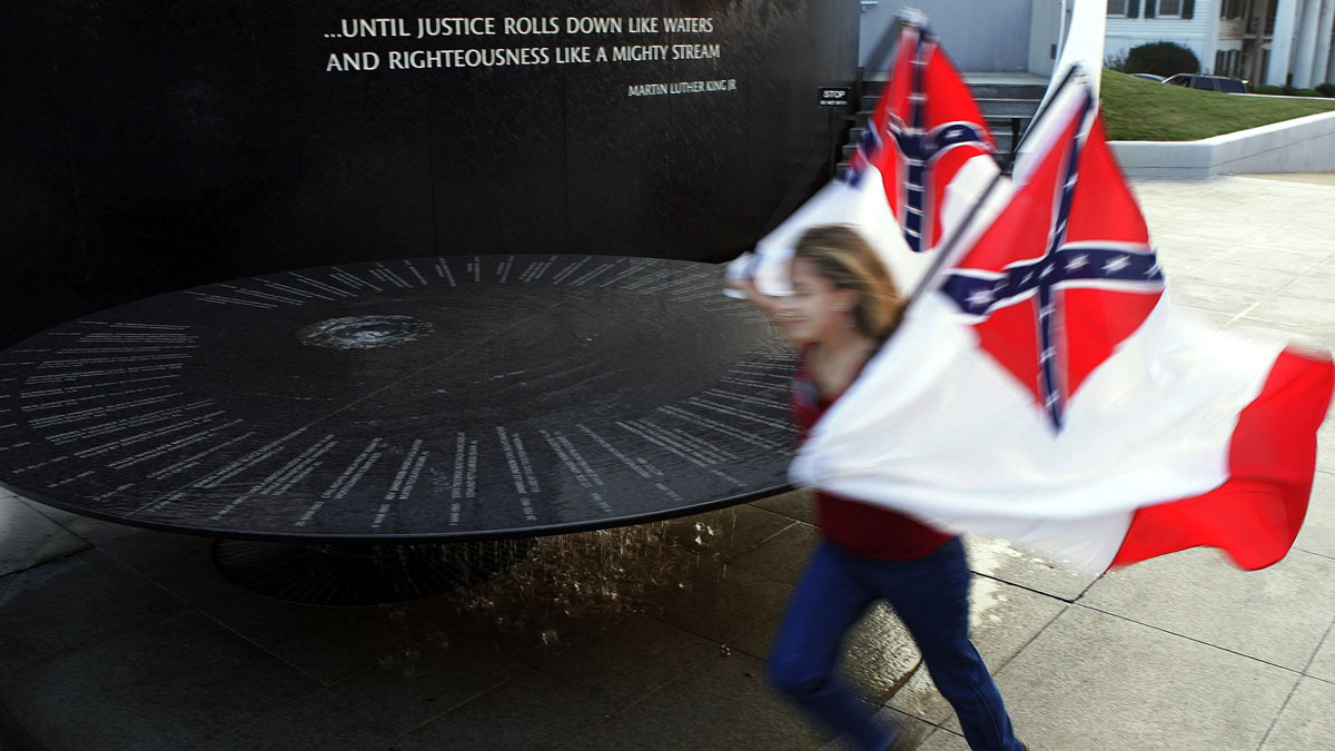 Anissa Jackson of Homer, Louisiana, carries Confederate battle flags as she runs past the Civil Rights Memorial outside the Southern Poverty Law Center in Montgomery, Alabama, on Friday, Oct. 22, 2004.