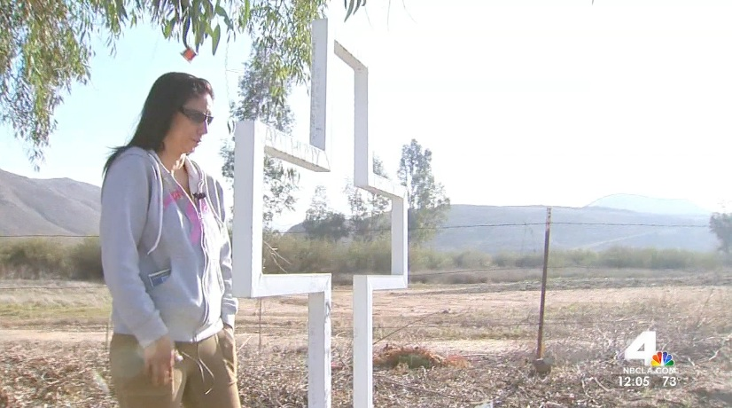 Ann Marie Devaney stands next to a cross n Thursday March 6, 2014 that she placed on a Lake Elsinore roadside near where her son was struck and killed.