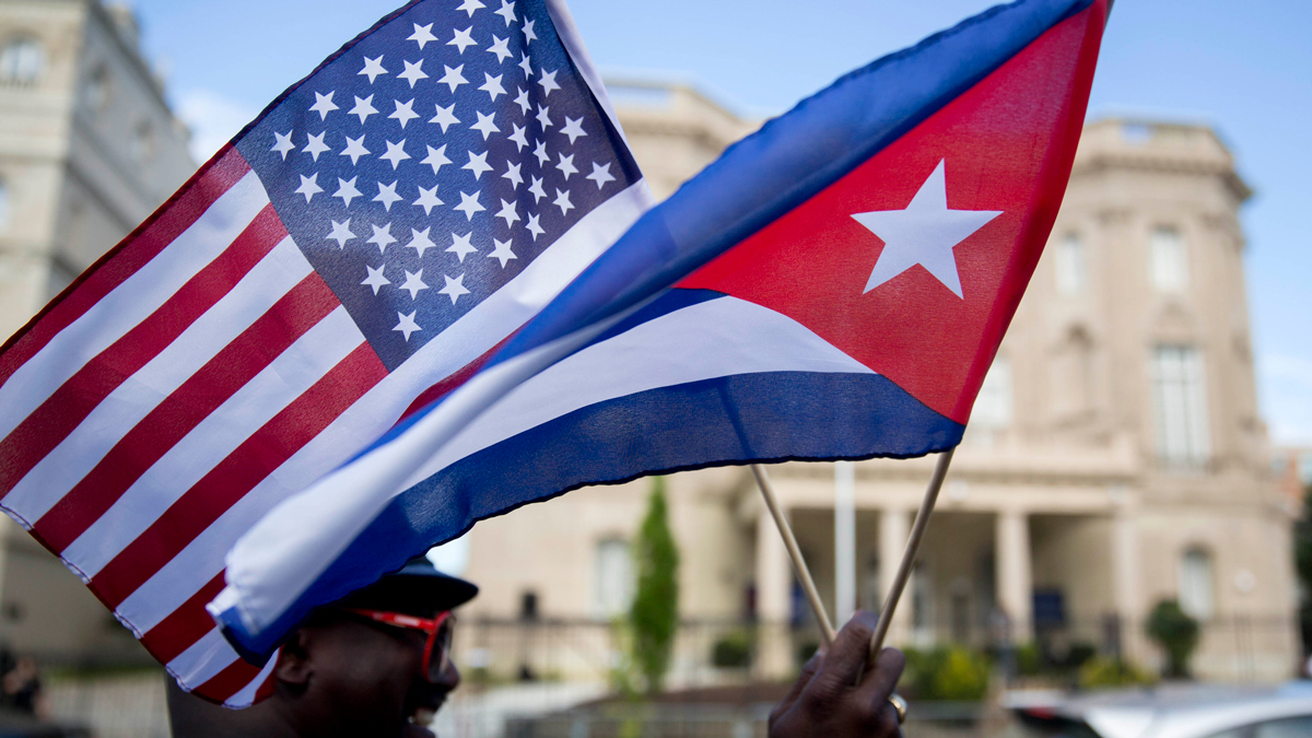 Eduardo Clark holds American and Cuban flags across the street from the Cuban embassy in Washington, D.C., U.S., on Monday, July 20, 2015.
