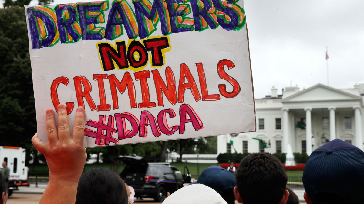 """FILE- In this Aug. 15, 2017, file photo, a woman holds up a signs in support of the Obama administration program known as Deferred Action for Childhood Arrivals, or DACA, during an immigration reform rally at the White House in Washington. After months of delays, President Donald Trump is expected to decide soon on the fate of so called """"dreamers"""" who were brought into the country illegally as children as he faces a looming court deadline and is digging in on appeals to his base. (AP Photo/Jacquelyn Martin, File)"""