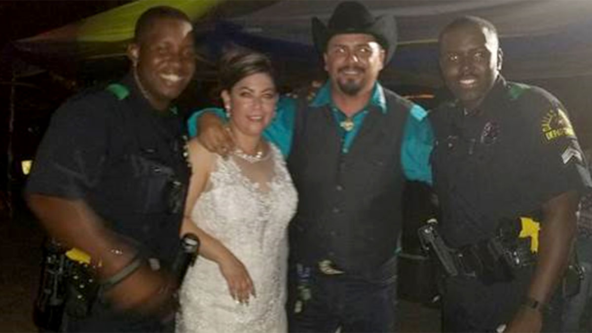 Dallas police officers pose with Gloria and Mario Hernandez after responding to a noise complaint at their wedding party.