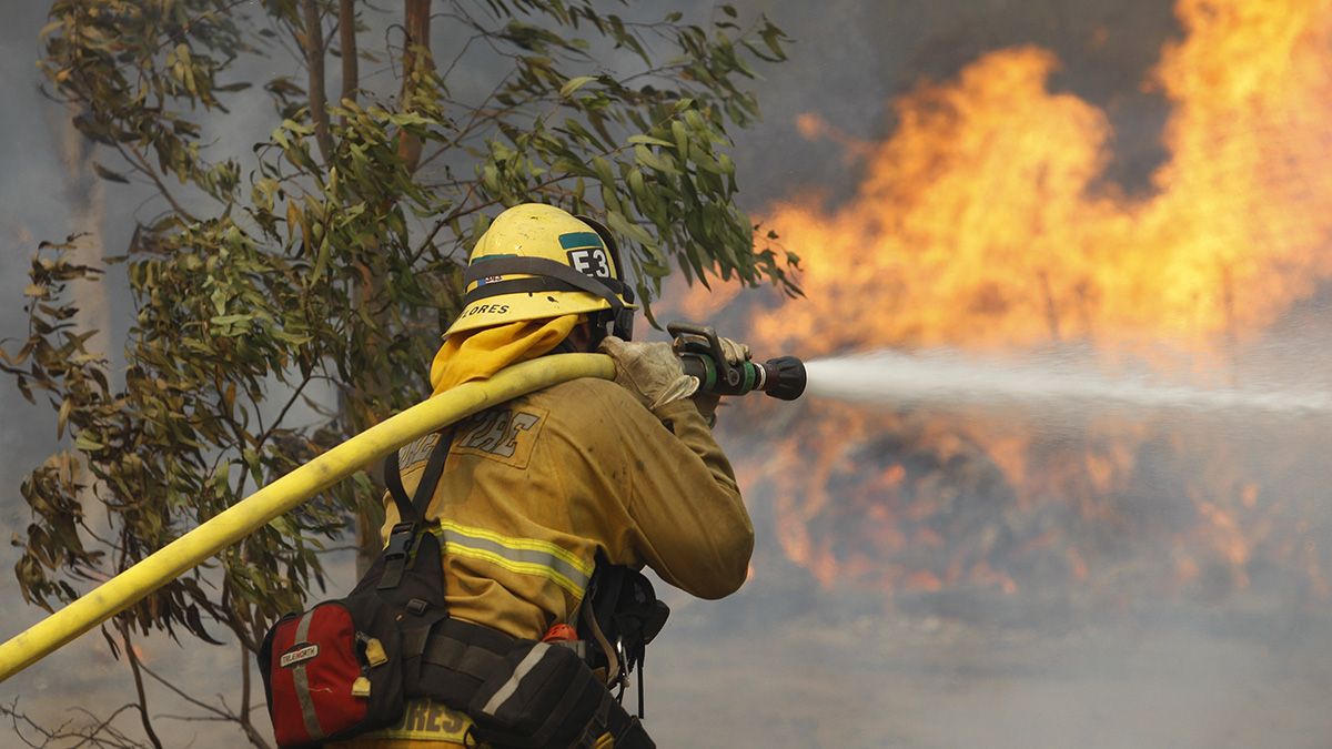 A firefighter hoses flames at the Cocos fire on May 15, 2014 in San Marcos, California.