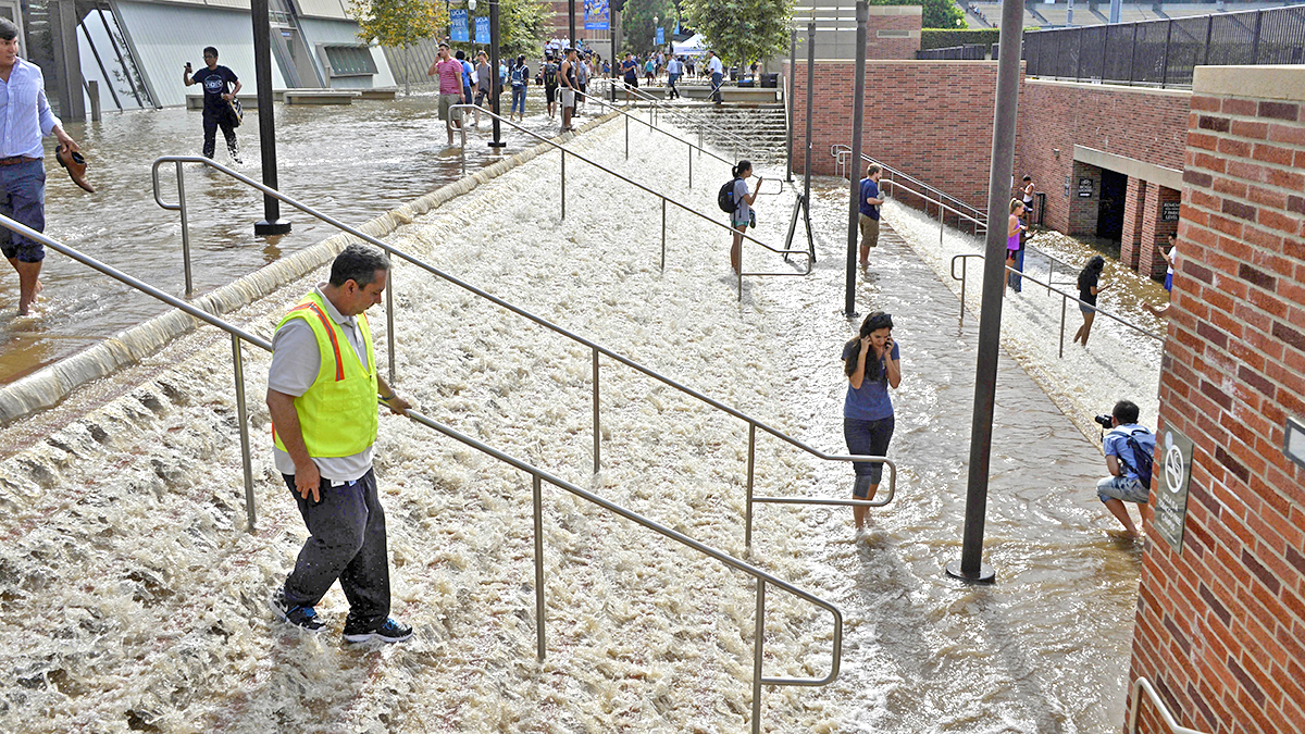 People walk down a stairway leading to a parking structure across from Pauley Pavilion on the UCLA campus after flooding from a broken 30-inch water main under nearby Sunset Boulevard inundated a large area of the campus in the Westwood section of Los Angeles, Tuesday, July 29, 2014.