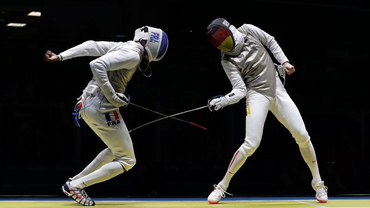Peter Joppich of Germany, right, competes with of Enzo Lefort France in the men's individual foil fencing event at the 2016 Summer Olympics in Rio de Janeiro, Brazil, Sunday, Aug. 7, 2016. Lefort dropped his phone during the event.