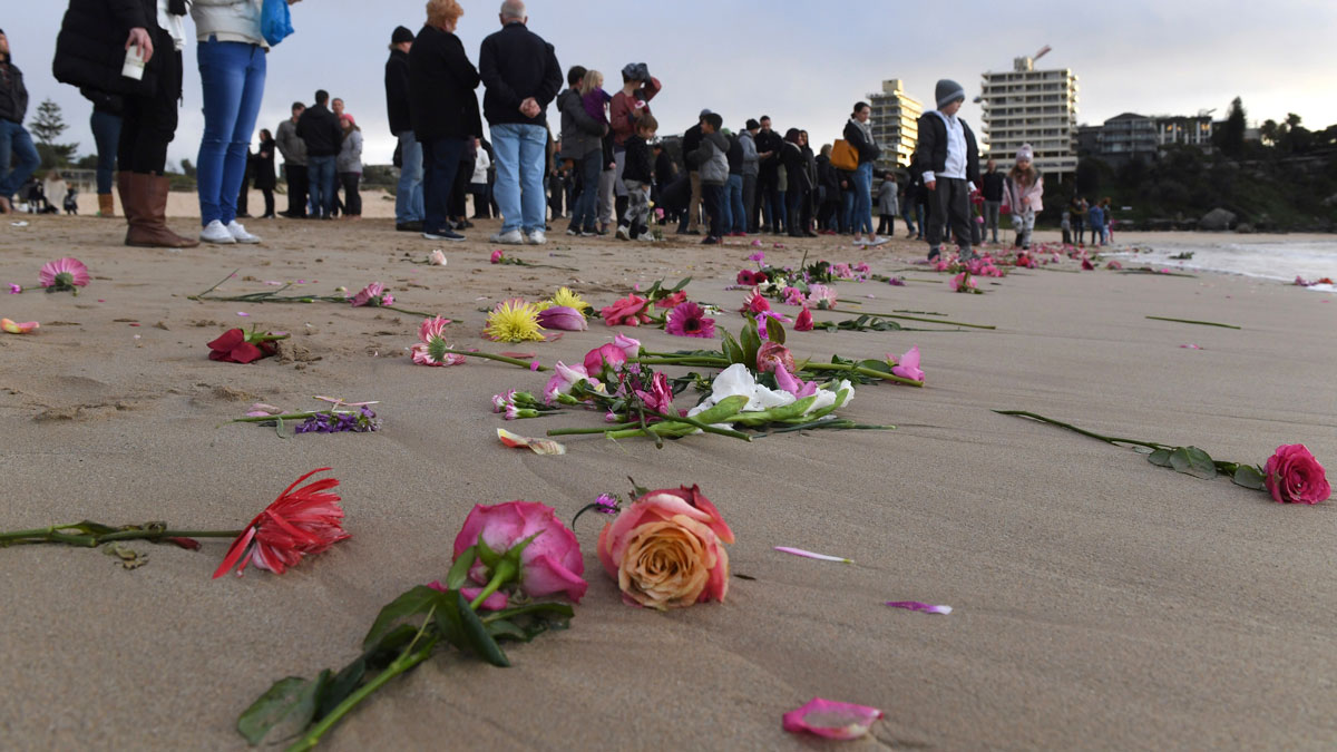 Family and friends gather on Sydney's Freshwater Beach, Wednesday, July 19, 2017, following a candlelight vigil, where they threw hundreds of pink flowers into the ocean for Justine Damond who was shot by a Minneapolis last weekend. Damond, a 40-year-old spiritual healer and bride-to-be, was shot Saturday night by one of the two officers responding to her 911 call. Damond had called police about what she thought was a sexual assault in the alley behind her home.