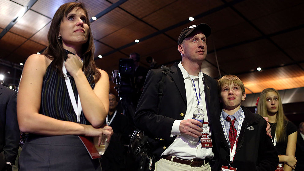 David French (center) — flanked by his wife Nancy, daughter Camille, and son Austin — reacts to the election results displayed on a television during Mitt Romney's campaign election night event in Boston, Massachusetts in this Nov. 6, 2012 file photo.