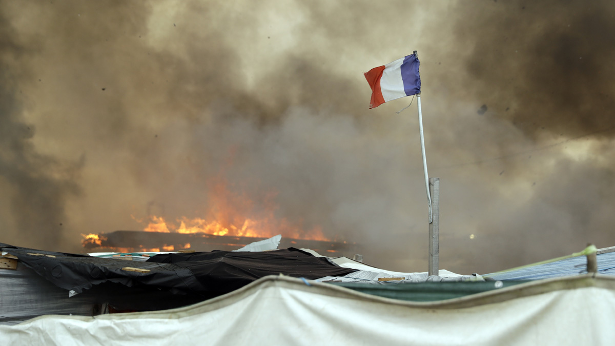 A French flag flutters while smoke billows from burning shelters set on fire by migrants in the makeshift migrant camp known as