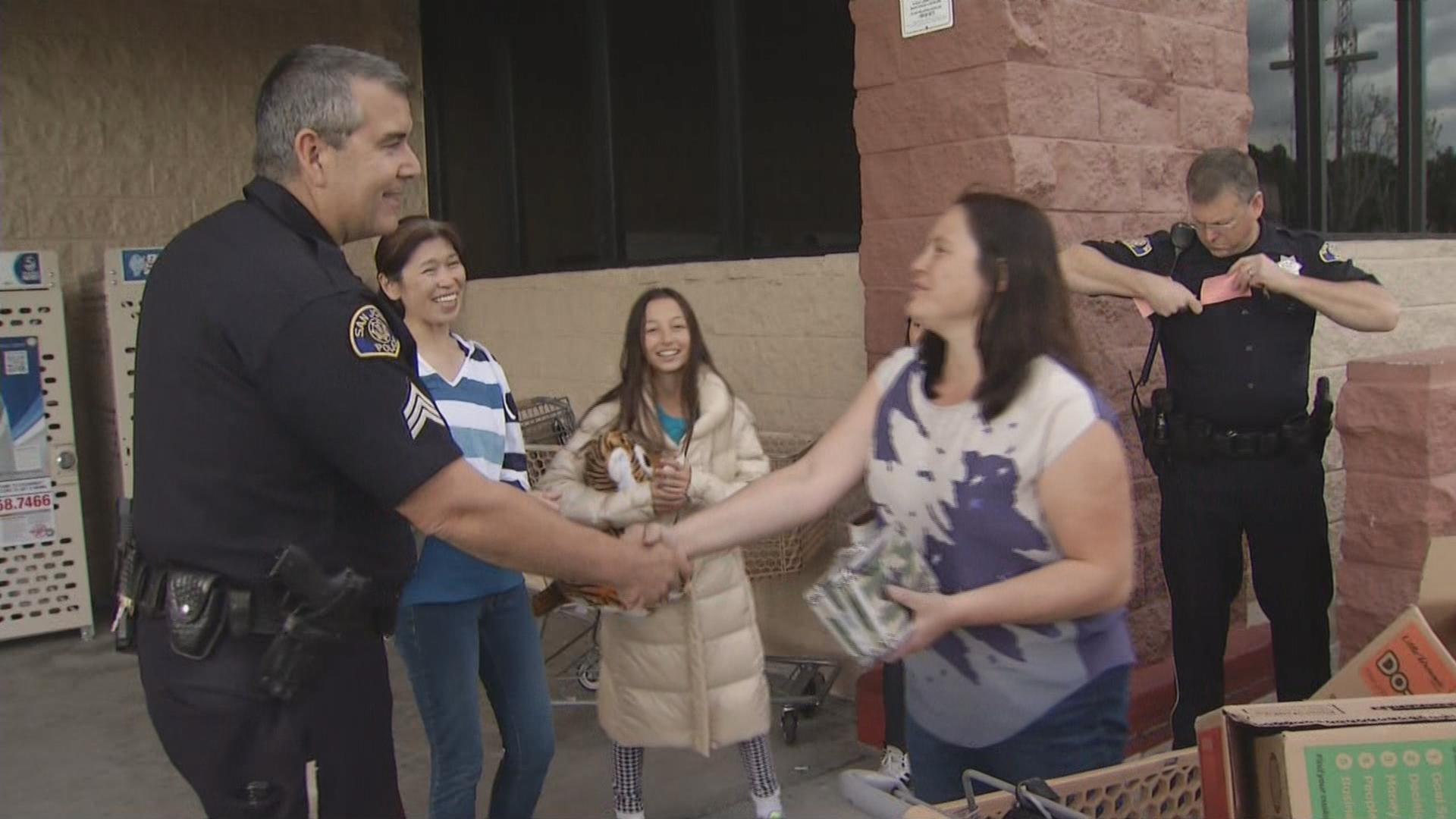 The mother of Sophia Contos shakes hands with a San Jose police officer who helped retrieve a stolen Girl Scout Cookies cash box.