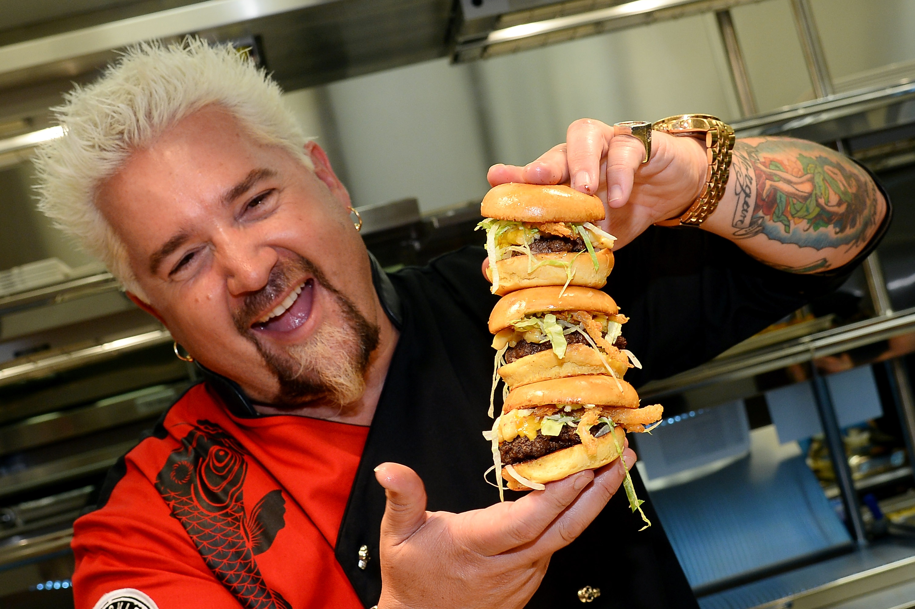 LAS VEGAS, NV - APRIL 04: Chef and television personality Guy Fieri holds hamburgers in the kitchen during a welcome event for Guy Fieri's Vegas Kitchen & Bar at The Quad Resort & Casino on April 4, 2014 in Las Vegas, Nevada. (Photo by Ethan Miller/Getty Images for Caesars Entertainment)