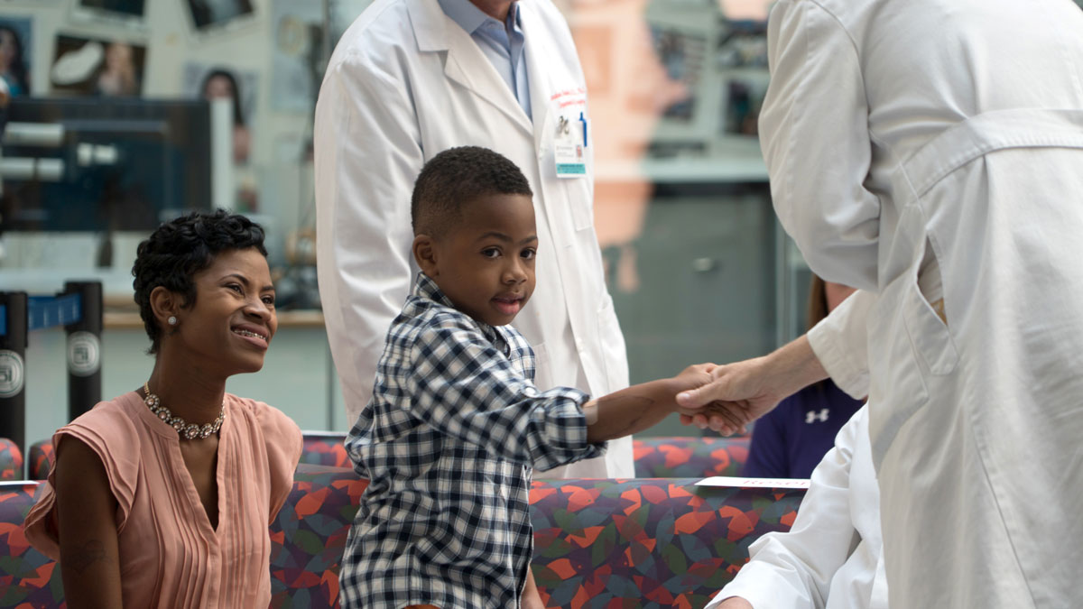 Zion Harvey, center, who received a double hand transplant in July 2015, shakes hands with a health care worker as his mother Pattie Ray, left, smiles during a news conference, Tuesday, Aug. 23, 2016 at The Children's Hospital of Philadelphia in Philadelphia.