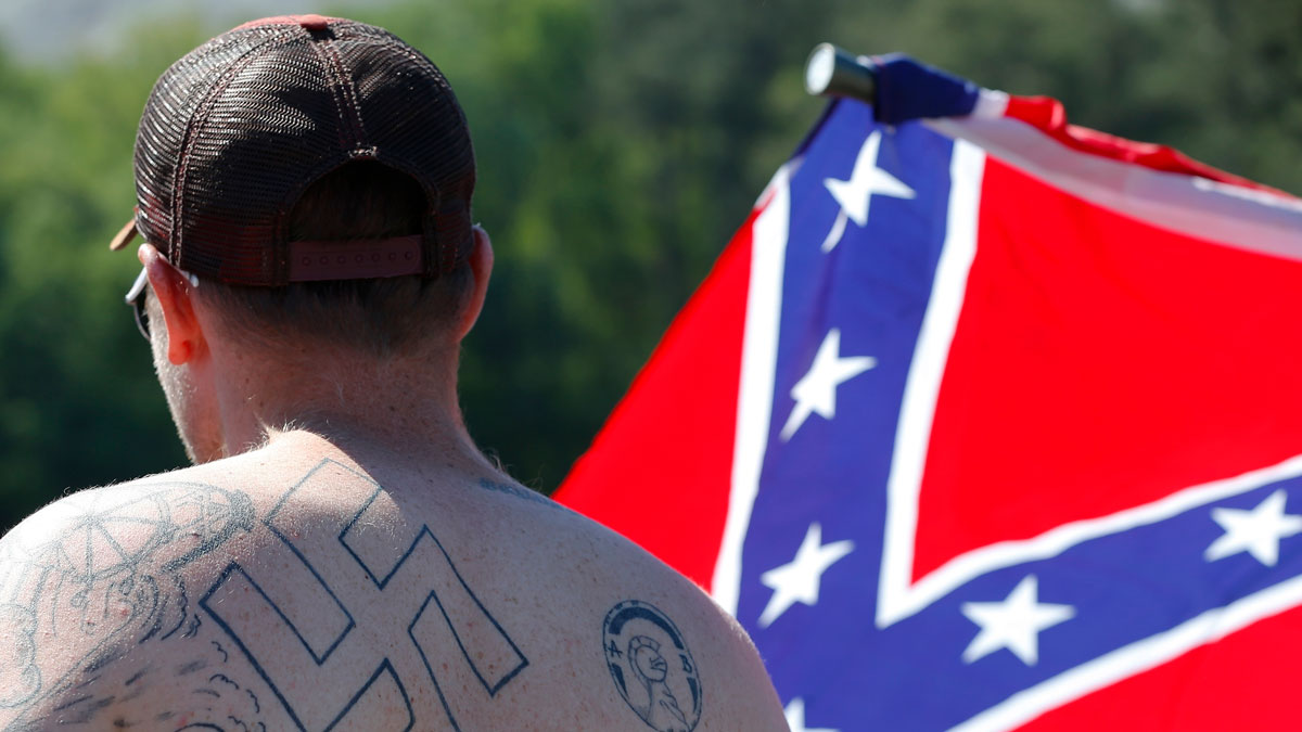 File Photo—In this April 23, 2016 photo, a man walks during a protest at Stone Mountain Park, in Stone Mountain, Ga.