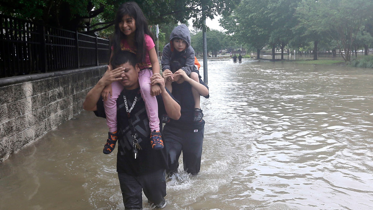 Jose Palacios, left, and his wife Rebecca, right, carry their children, Ariana and Aaron, through floodwaters as they evacuate their flooded apartment complex Monday, April 18, 2016, in Houston.