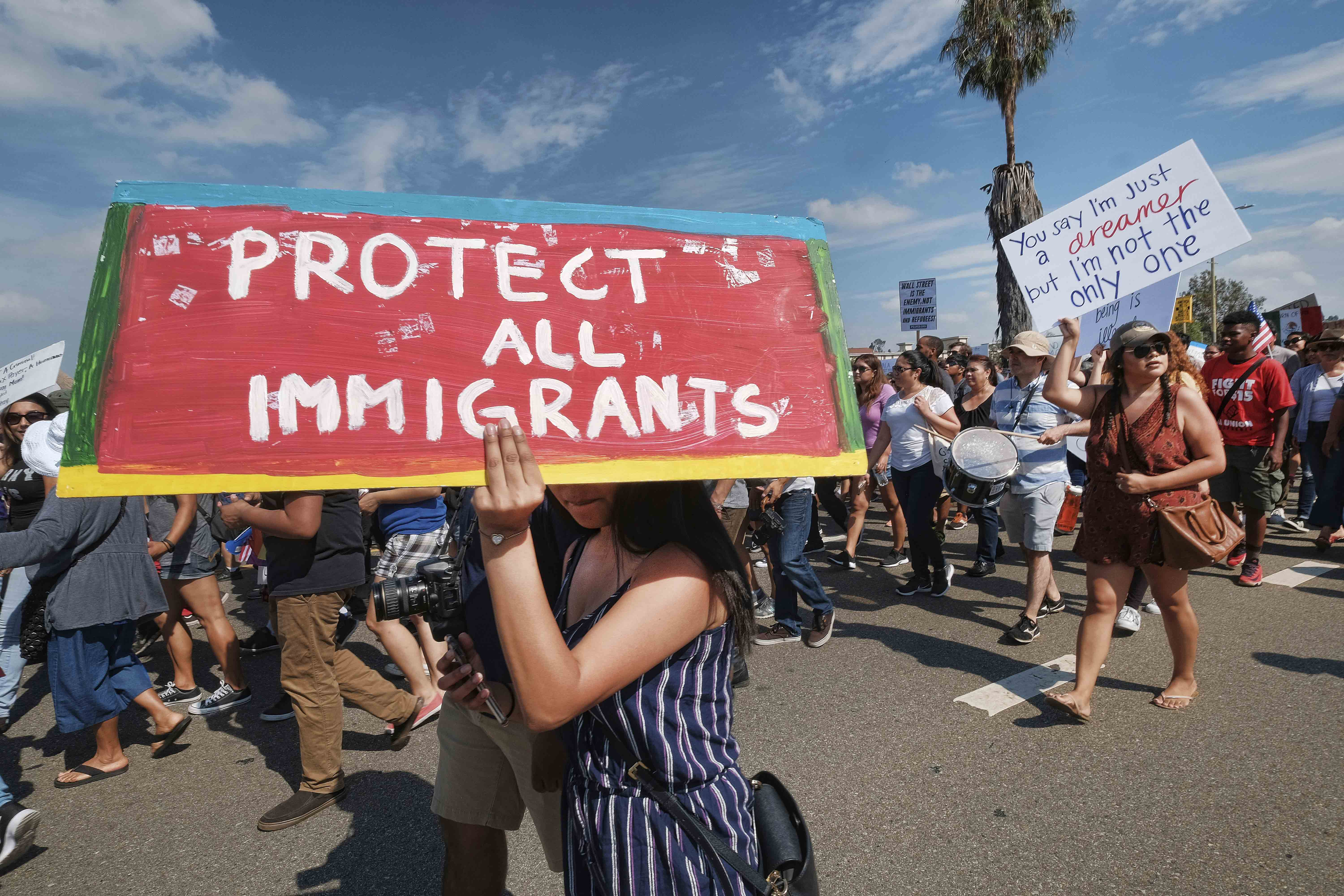 Supporters of the Deferred Action for Childhood Arrivals, or DACA chant slogans and carry signs while joining a Labor Day rally in downtown Los Angeles, Monday, Sept. 4, 2017.